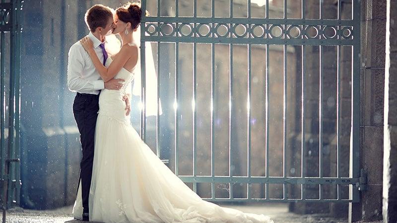 抱き合いキスする花嫁と花婿
