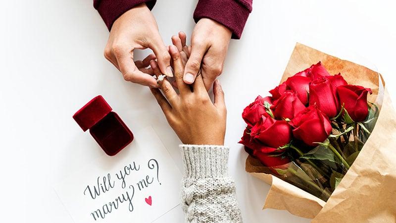恋人にプロポーズして婚約指輪を渡す男性