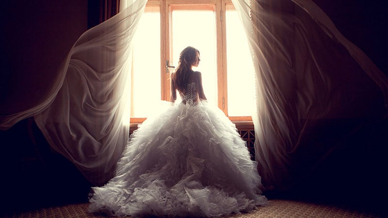 ウェディングドレス姿で窓辺に一人立っている女性