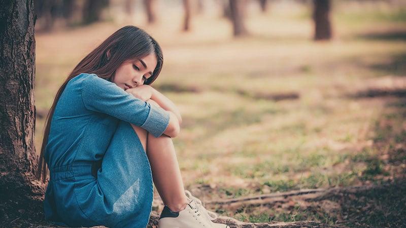 一人で膝を抱えて座り込む女性