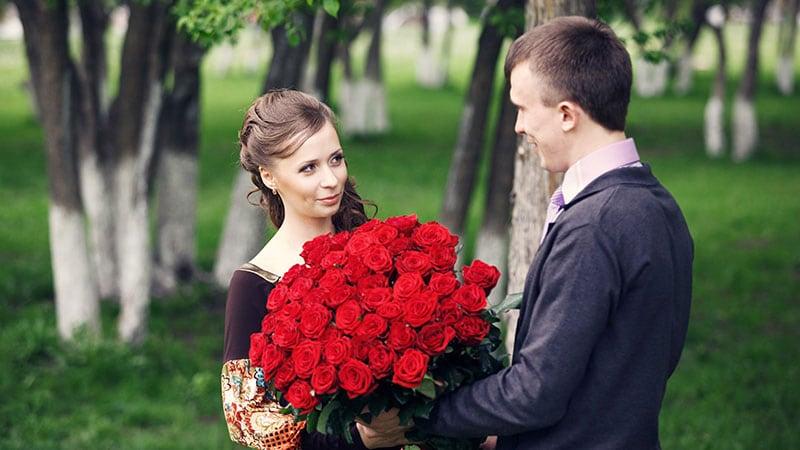 花束を持ってプロポーズする男性