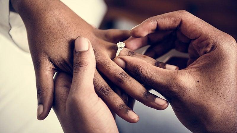女性の左手の薬指に指輪をはめる男性