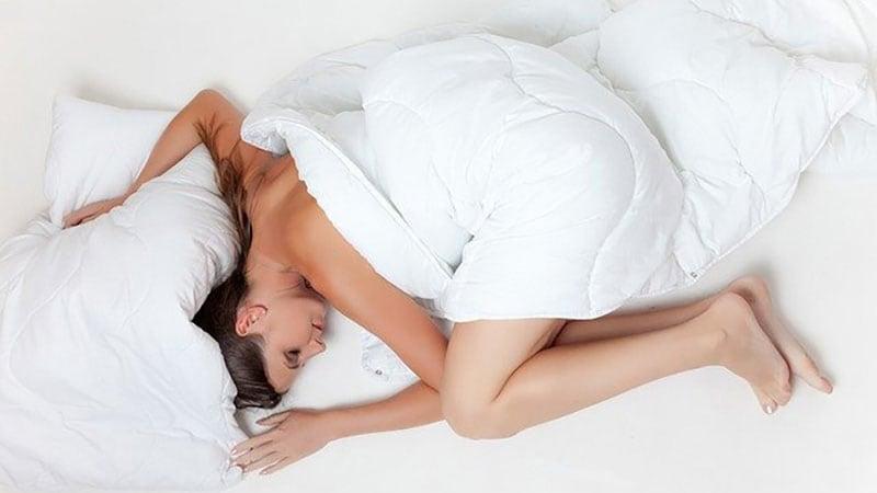 ベッドで眠る裸の女性