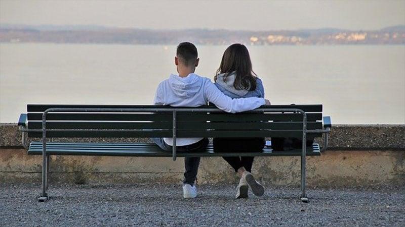 ベンチに並んで座るデート中の男女
