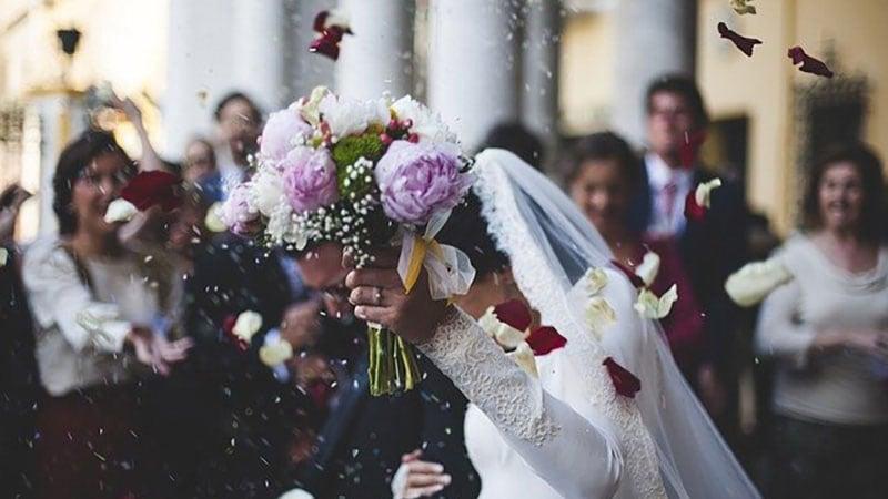 周囲に祝福されながら結婚する花嫁と花婿
