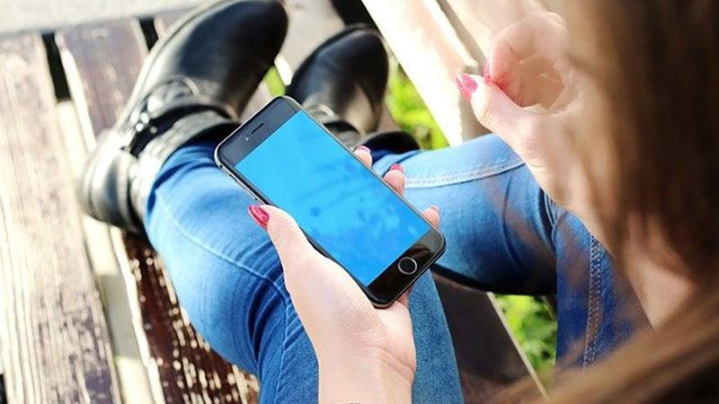 スマートフォンを片手に物思いにふける女性