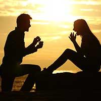 海に沈む夕日と恋人からプロポーズを受ける女性