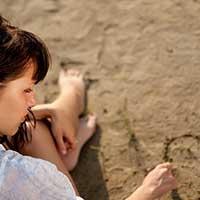 浜辺で片想いの相手のことを思い出す女性